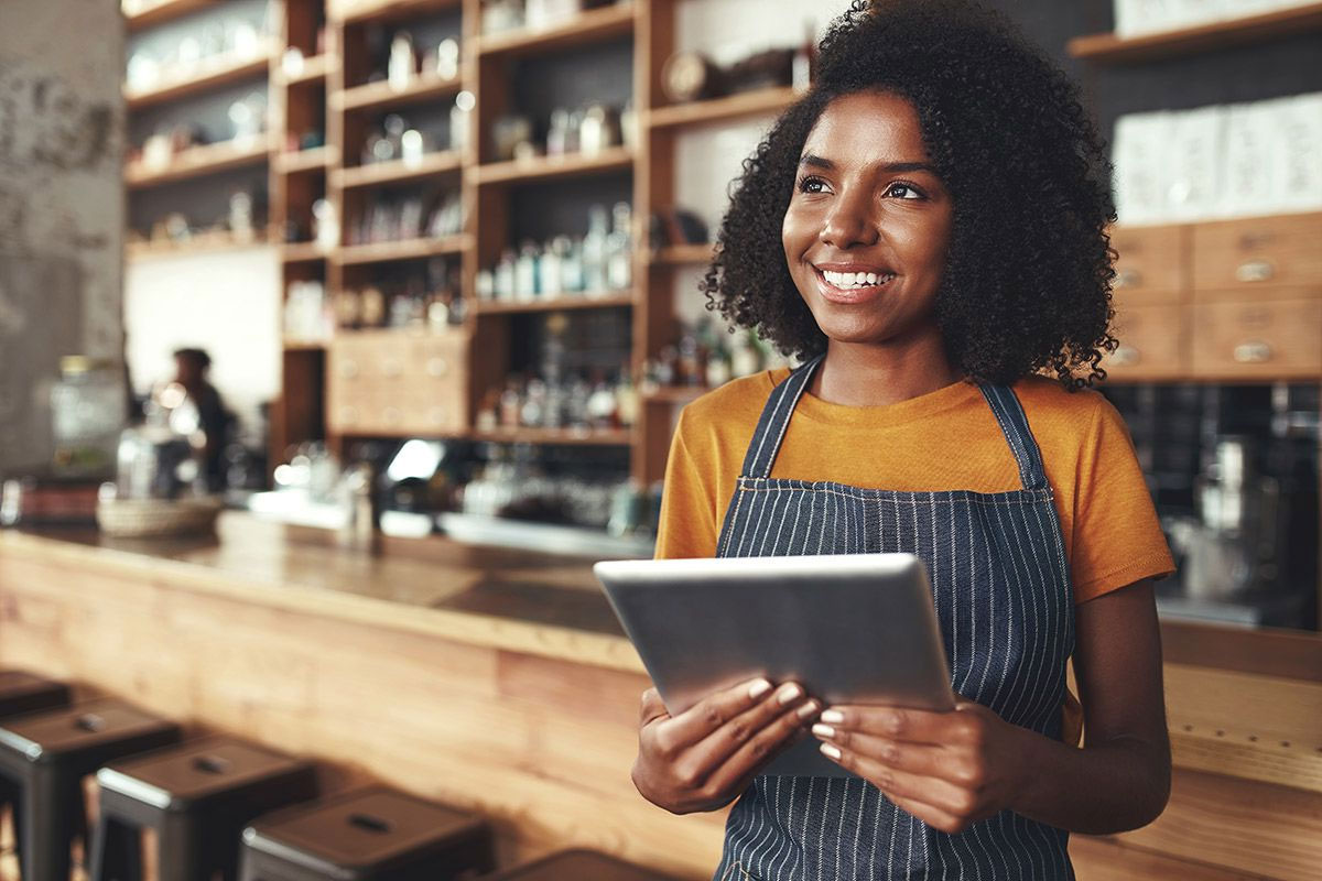 African American Woman Business Owner in Her 20s Wearing a Grey Apron and Holding a Silver Tablet in a Coffee Shop